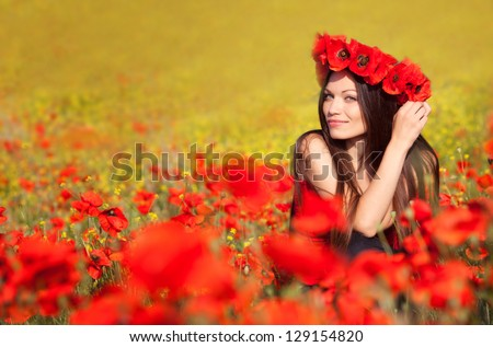 Beautiful girl on the poppy field