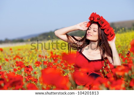 Beautiful girl on the poppy meadow