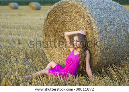 beautiful girl on the reaped field of the cereal crop - stock photo
