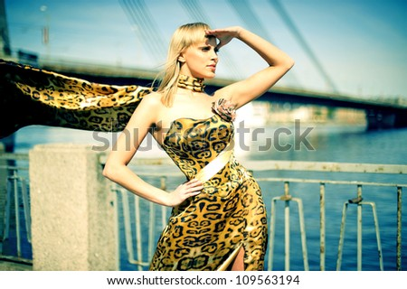 beautiful girl on the riverbank in the town in leopard dress is waiting fora man - stock photo