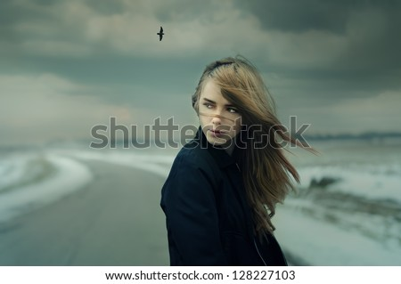 beautiful girl on the road in cold windy weather. Photo Gothic