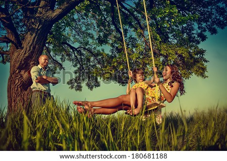 Beautiful girl on the swing in the forest with her parents  - stock photo