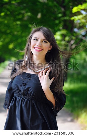 Beautiful girl outdoors spring portrait, young woman with flowers in green park, spring concept. cheerful teenager walking outdoor.  - stock photo