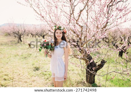 Beautiful girl outdoors spring portrait, young woman with flowers in green park, spring concept. cheerful teenager walking outdoor. series in portfolio - stock photo