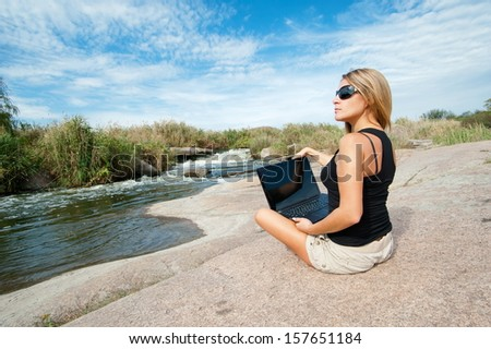 Beautiful girl outdoors with a laptop sitting on a rock - stock photo