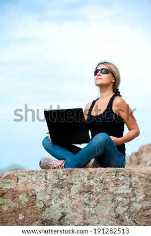 Beautiful girl outdoors with a laptop sitting on a rock
