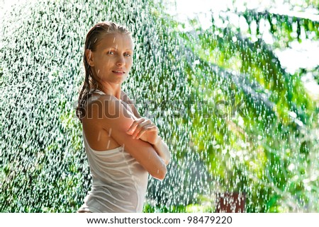 Beautiful girl outside under rain drops in tropical forest - stock photo