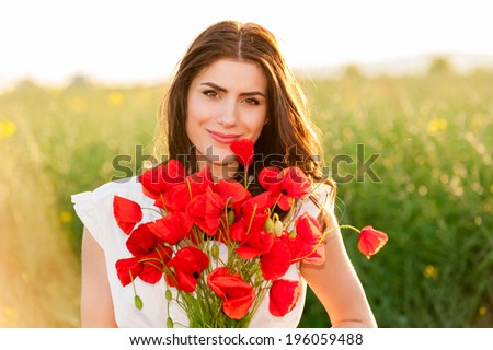 Beautiful Girl over Sky and Sunset  in the field holding a poppies bouquet and smiling Free Happy Woman Enjoying Nature. Beauty Girl Outdoor.  Freedom concept. Series.