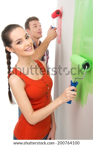 beautiful girl painting wall and smiling. couple using painting roller to color wall - stock photo