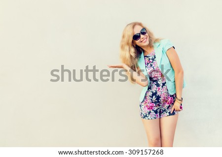 Beautiful girl. Photo of beautiful girl in fashionable clothes, glass in hand, against the background of a gray wall. Girl with beautiful long hair. Fashionable girl. Toning. Cheerful girl. - stock photo