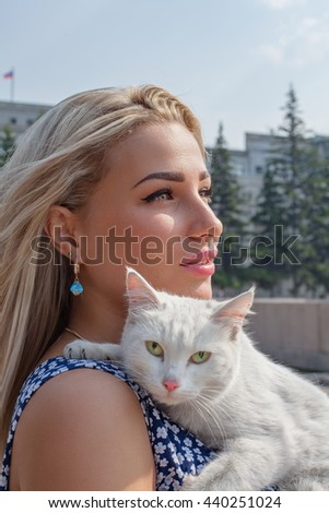 Beautiful girl picked up a stray cat - stock photo