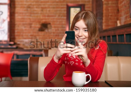 Beautiful girl picking up sms on mobile phone in cafe. - stock photo