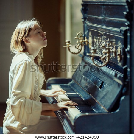 Beautiful girl playing ancient piano. Music concept