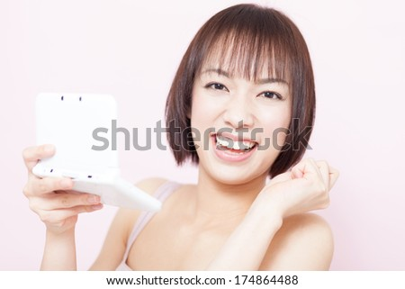 beautiful girl playing handheld video game against pink background - stock photo