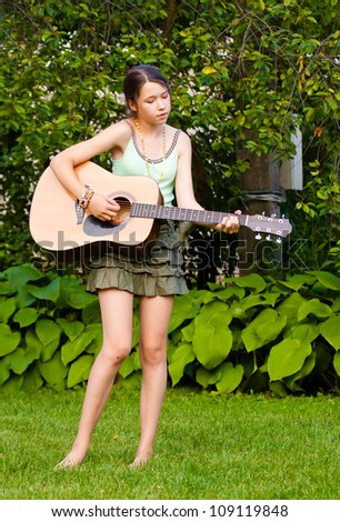 Beautiful girl playing the guitar and singing in the park - stock photo