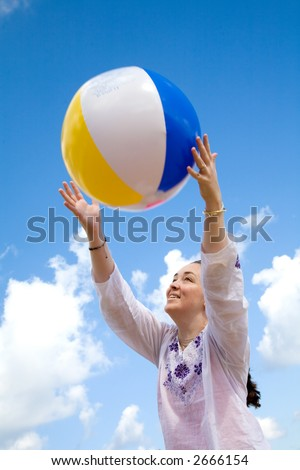 beautiful girl playing with a beachball at the beach in front of a beautiful blue sky