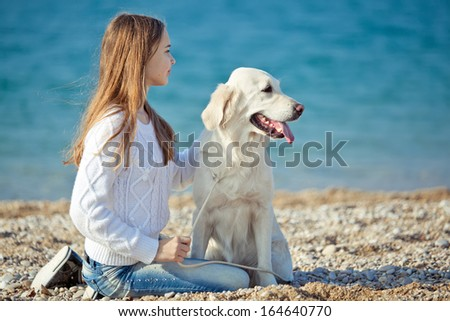 Beautiful girl playing with a dog. Outdoor portrait. series - stock photo