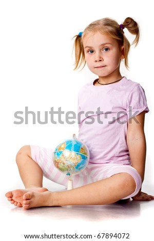 Beautiful girl playing with a globe, pointing a continent