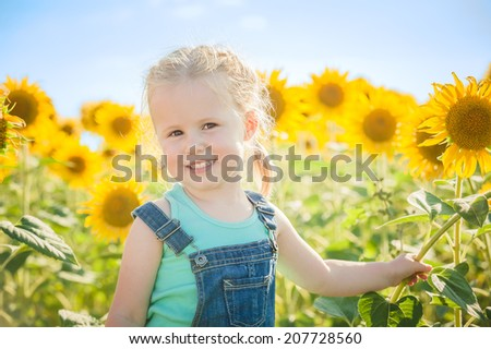 Beautiful girl plays with the sunflowers in a summer day
