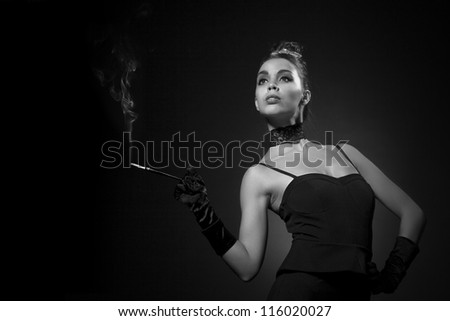 Beautiful girl  portrait in retro style. Glamorous woman in black outfit holding a cigarette