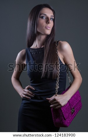 Beautiful girl posing and holding pink bag - stock photo