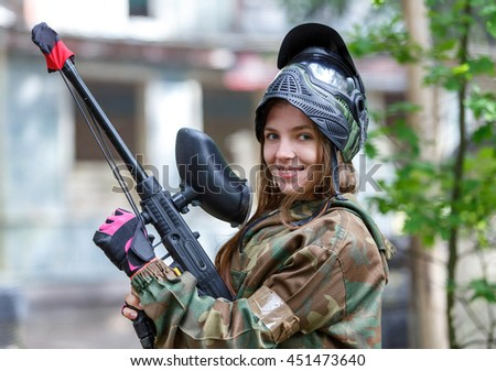 Beautiful girl posing in paintball ammunition outdoors - stock photo