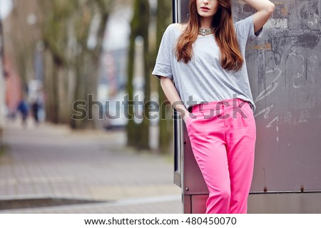 Beautiful girl posing in pink pants and grey top on the street