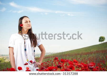 Beautiful girl posing in poppy field - stock photo