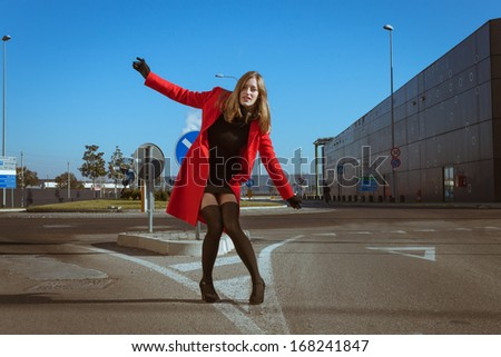 Beautiful girl posing in the street with red coat