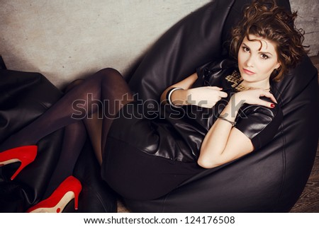 beautiful girl posing lying in the studio in the fashionable leather dress and red shoes. - stock photo