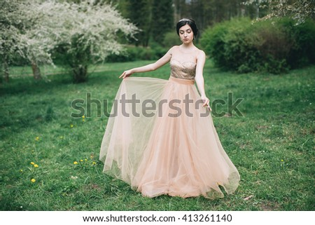 Beautiful girl posing near blossoming tree in spring