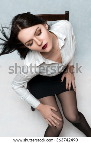 beautiful girl posing on a chair in the studio