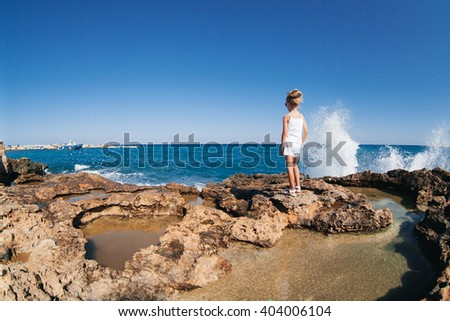 Beautiful girl posing on the rocky seashore with water splash