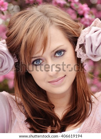 Beautiful girl posing over spring flowers background - stock photo