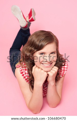 Beautiful girl posing with hands on chin. Lying on studio floor - stock photo