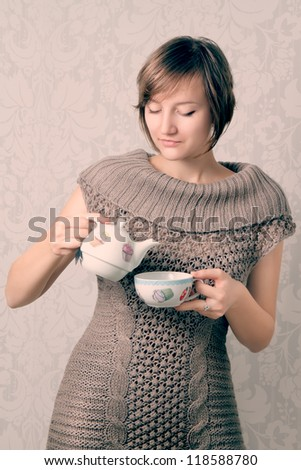 Beautiful Girl  pouring Tea. Cup of Hot Beverage