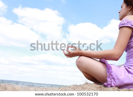 Beautiful girl practicing yoga on the beach - stock photo