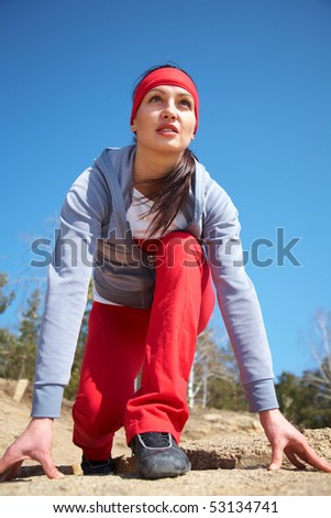 beautiful girl preparing to start on the race track and firmly looks forward - stock photo