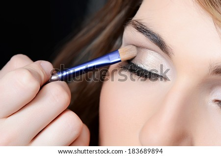 Beautiful girl put the makeup on the face - stock photo