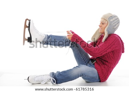 Beautiful girl puts on skates. Isolated on white background - stock photo