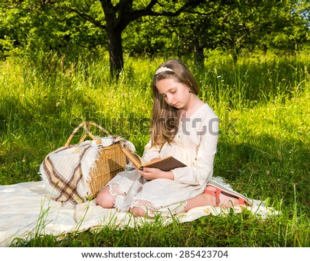 Beautiful girl reading a book at the park
