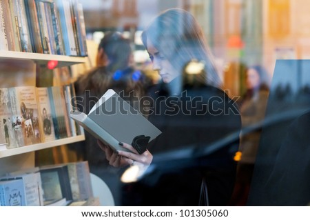 Beautiful girl reading a book in a bookstore - stock photo