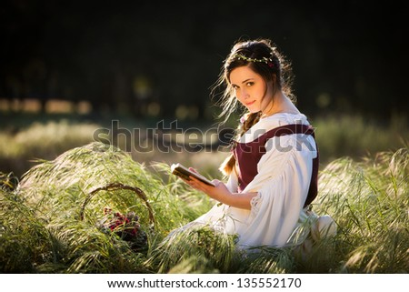 Beautiful girl reading a book in a country setting, dressed in historical clothing - stock photo
