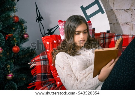 Beautiful girl reading a book lying on the couch, covered with plaid. Winter holidays, New Year, a large clock. Interior room
