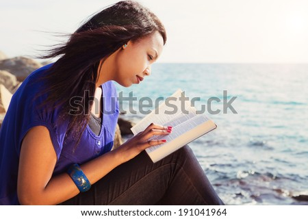 Beautiful Girl reading her Bible by the sea - stock photo