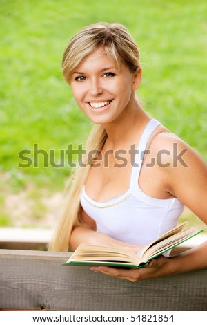 Beautiful girl reads book on bench against summer nature.
