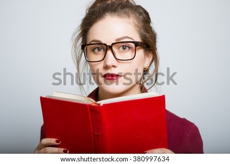 Beautiful girl reads red book, isolated on a gray background
