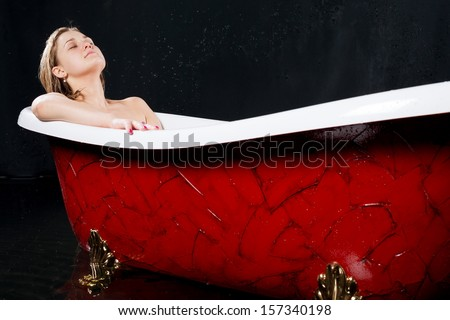 Beautiful girl relaxes in the red bathtub - stock photo