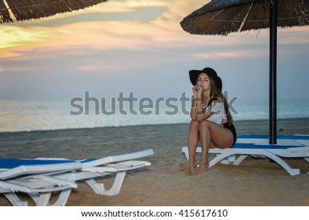 Beautiful girl relaxing at the beach, lounge and natural parasol umbrella background. Happy vacation travel