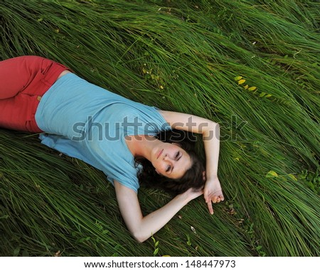 Beautiful girl relaxing lying in the field. Beauty Model Woman Face with freckles.